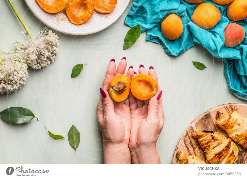 Hands holding halved apricot with pit Food Fruit Croissant Nutrition Crockery Style Human being Woman Adults Design Apricot Division Kernels & Pits & Stones