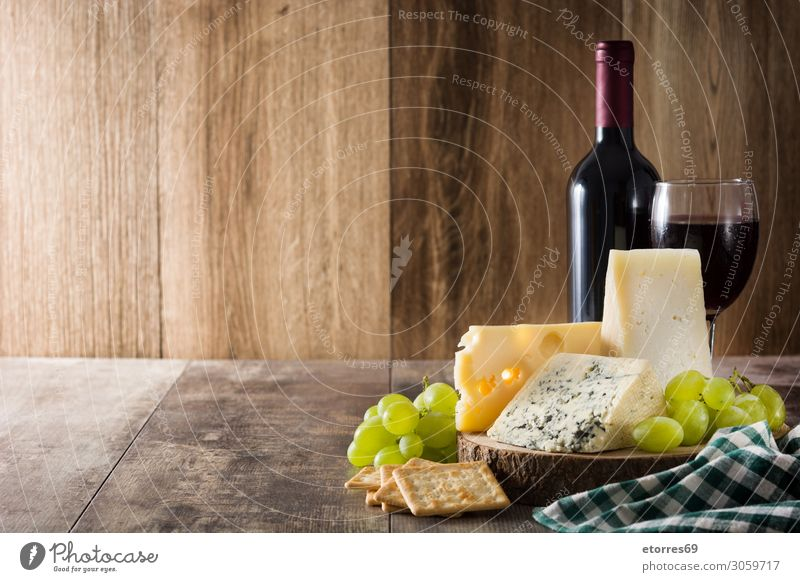 Assortment of cheeses and wine on wooden table. Cheese Wine Food Healthy Eating Food photograph Beverage Alcoholic drinks assortment Wood Bottle french Gourmet