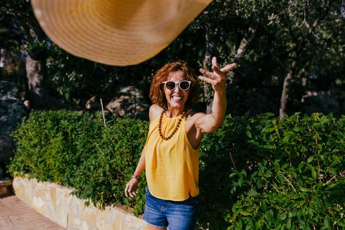 Beautiful girl at sunset holding a hat in her hand and throwing it to the camera. Summer, fun and lifestyle outdoors Freedom Human being Smiling