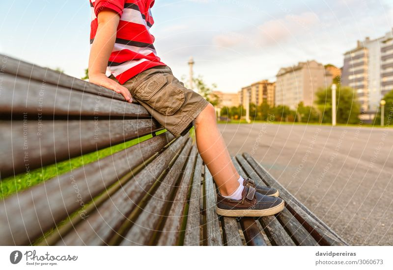 Boy legs sitting on the top of bench park relaxing Lifestyle Beautiful Relaxation Summer Garden Child Human being Boy (child) Infancy Feet Nature Park Pants