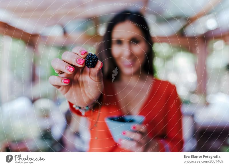 young woman holding a bowl of blackberries. preparing a healthy recipe of diverse fruits, watermelon, orange and blackberries. Using a mixer. Homemade, indoors, healthy lifestyle. selective focus