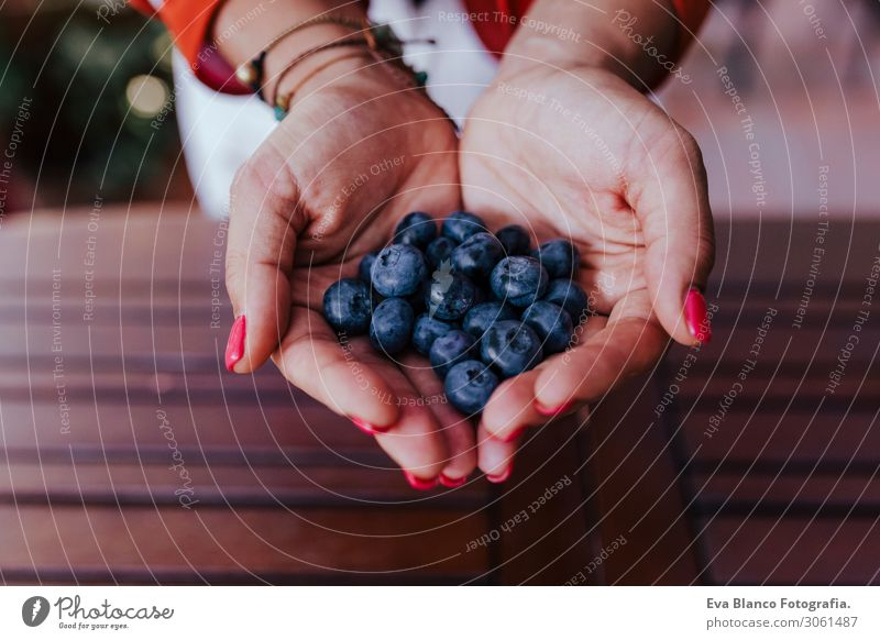 young woman holding a bowl of blueberries. preparing a healthy recipe of diverse fruits, watermelon, orange and blackberries. Using a mixer. Homemade, indoors, healthy lifestyle