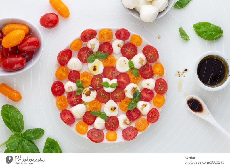 Tomato with mozzarella, basil and dressing with balsamic vinegar on white round plate with ingredients Lettuce Mozzarella Dressing Salad Herbs and spices Cheese