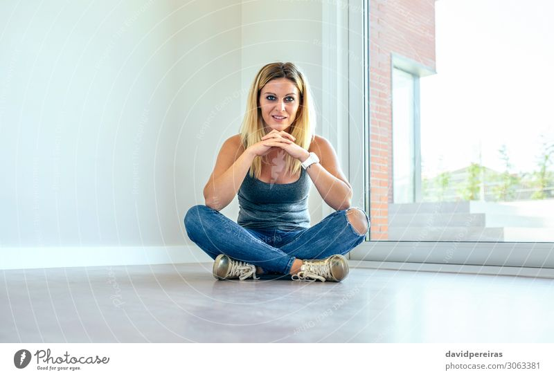 Thoughtful girl sitting in a living room Beautiful Contentment House (Residential Structure) Human being Woman Adults Hand Jeans Sneakers Blonde Wood Observe