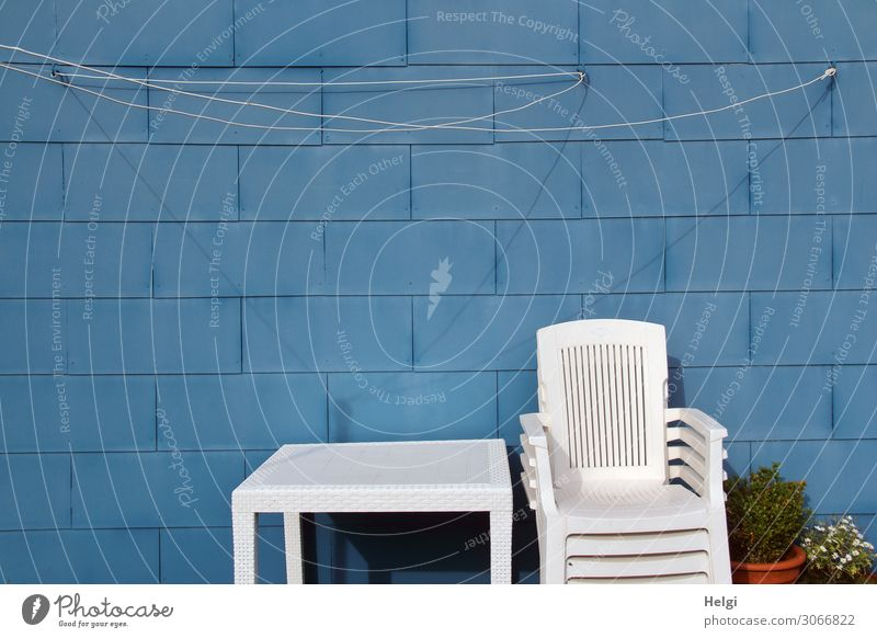 stacked white plastic chairs and a white table in front of a blue wall with clothesline Village House (Residential Structure) Wall (barrier) Wall (building)