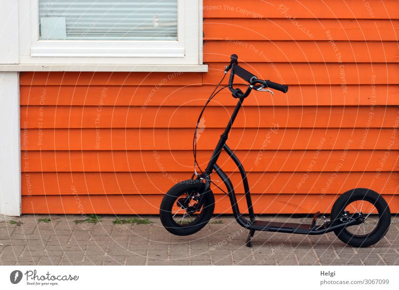 black scooter stands in front of a wooden orange wooden wall with window House (Residential Structure) Wall (barrier) Wall (building) Facade Window Footpath