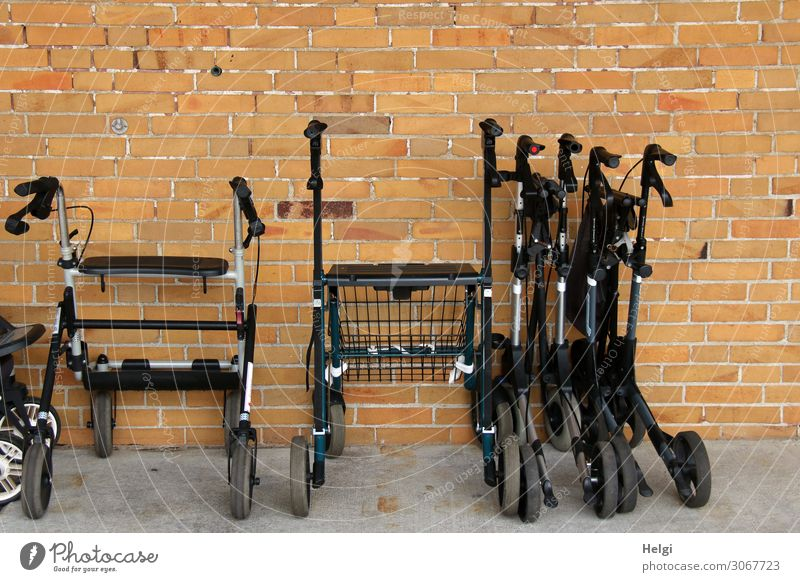 various rollators, some folded up, stand in front of a stone wall Wall (barrier) Wall (building) Stand Wait Authentic Exceptional Uniqueness Brown Gray Black