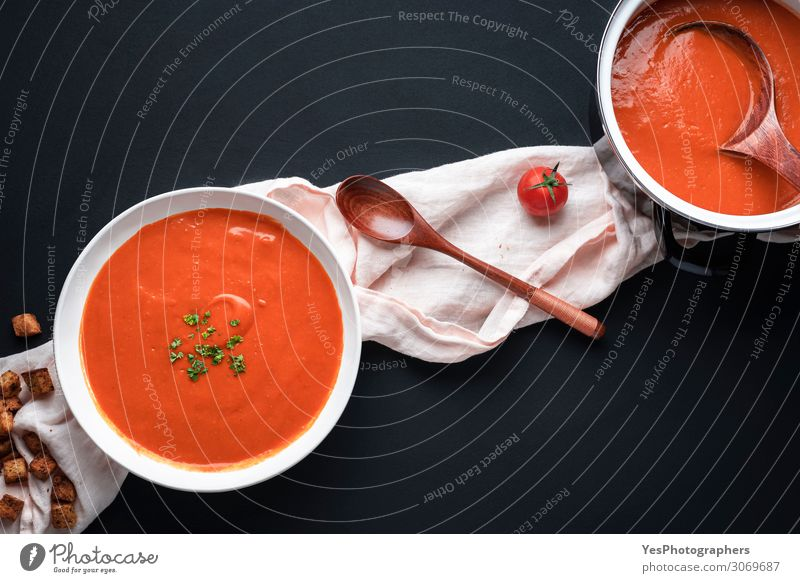 Tomato soup on black table. Healthy homemade soup Vegetable Soup Stew Herbs and spices Nutrition Lunch Dinner Vegetarian diet Diet Crockery Bowl Pot Spoon