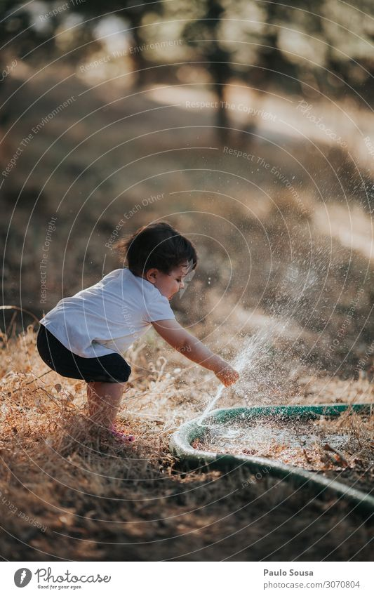 Child playing with water hose Lifestyle Human being Toddler Girl 1 1 - 3 years Summer Touch To enjoy Playing Happiness Happy Funny Curiosity Wild Self-confident