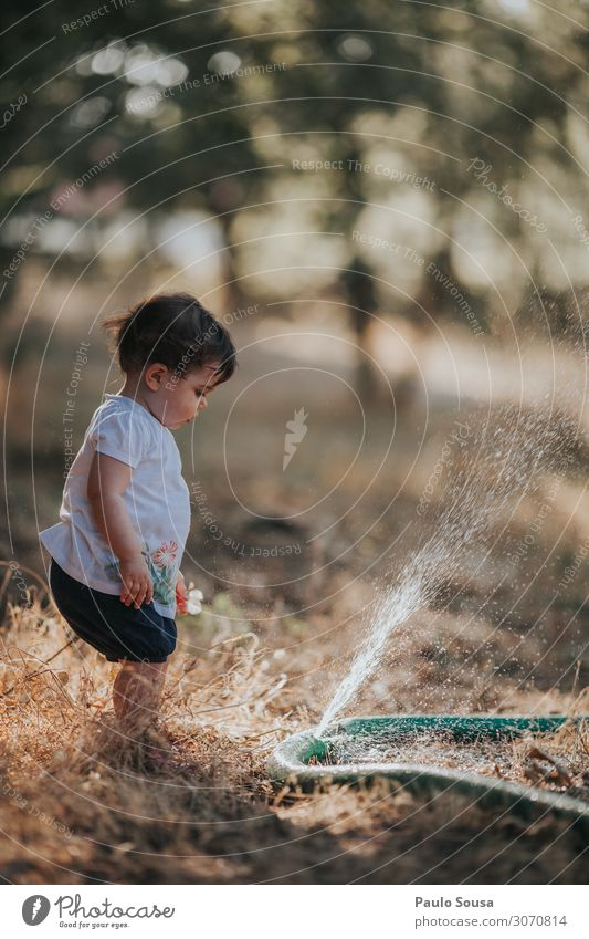 Baby Girl Standing By Water Spraying From Hose On Land Child childhood Summer Summer vacation Summer's day Exterior shot Colour photo Summery Infancy Nature