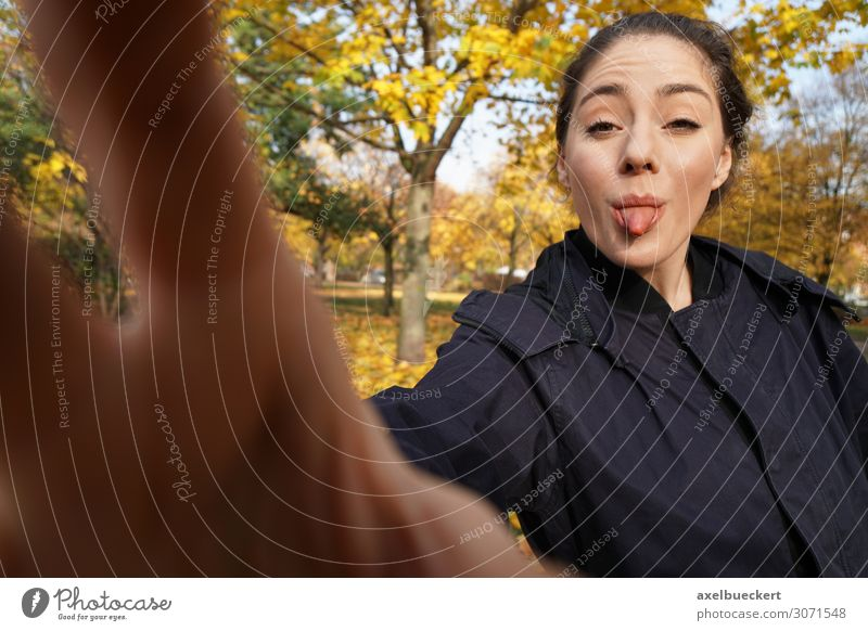 young woman sticks out her tongue with a camera - no photos stick out one's tongue Brash Take a photo Funny Selfie by hand Lifestyle Joy Leisure and hobbies