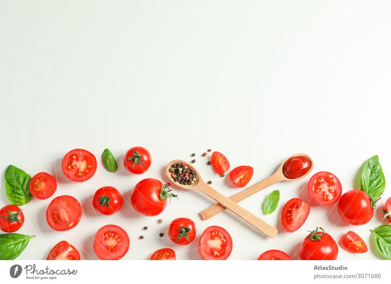 Flat lay composition with fresh tomatoes, pepper, basil and wooden spoons on white background, space for text. Ripe vegetables spice garlic sauce cooking red
