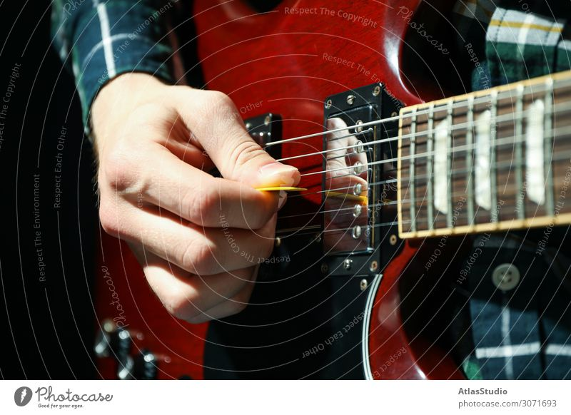 Man playing on electric guitar against dark background, closeup instrument flare live pick musician young table space blues song solo text player accessories