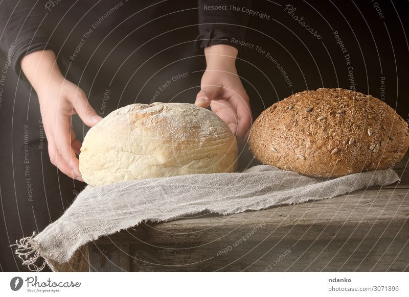 two female hands lay on a table baked white round bread Dough Baked goods Bread Breakfast Sun Table Kitchen Human being Woman Adults Arm Hand Wood Old Eating