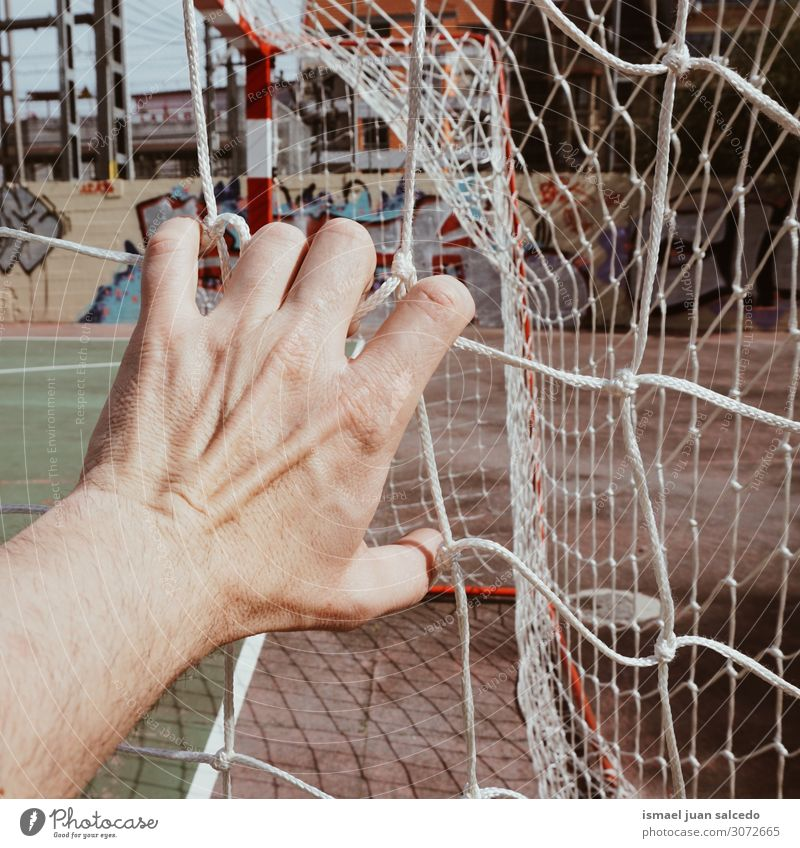 hand grabbing a soccer rope net in the field Hand Man Human being Fingers Body Arm Rope Net Internet Sports equipment tied tangled Street Exterior shot