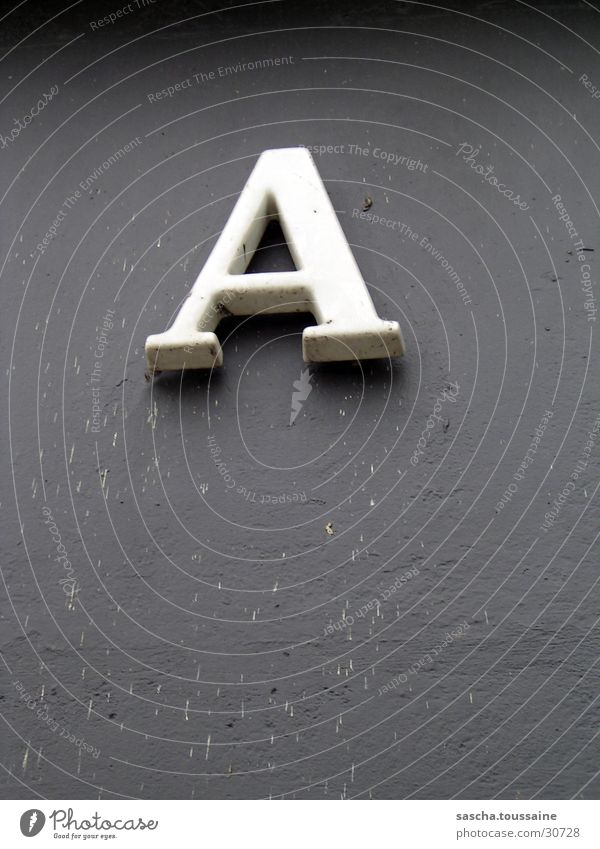 A of course... Letters (alphabet) House number Wall (building) Gray White Things Shadow Dirty