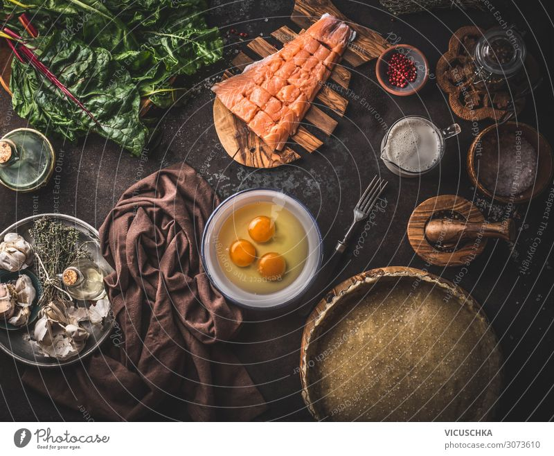 Quiche or open faced pie ingredients: salmon, chard, eggs, cream, dough in baking form on dark rustic table background with kitchen utensils, top view. Cooking preparation