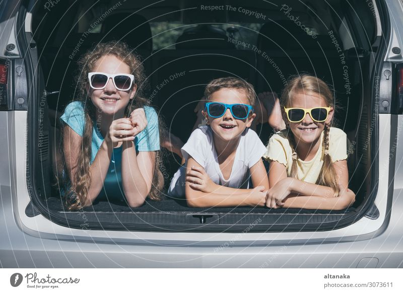 Happy brother and his two sisters are sitting in the car at the day time. Children having fun outdoors. Concept of the family is ready for travel. Lifestyle Joy