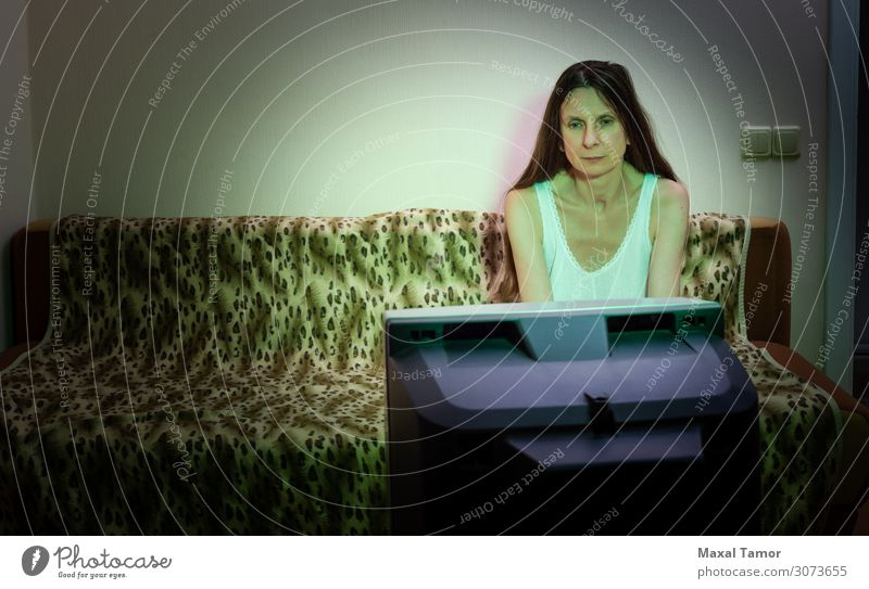 A middle-aged woman, alone, watches television Lifestyle Face Relaxation Leisure and hobbies Sofa Audience TV set Screen Human being Woman Adults Media