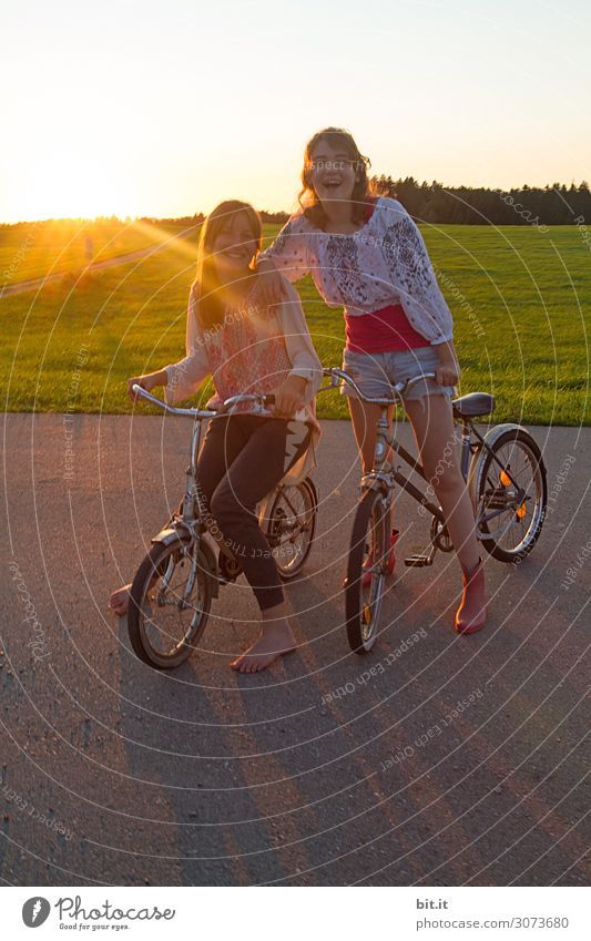 Two girls on bicycles, in nature at sunset. Vacation & Travel Trip Adventure Far-off places Freedom Joy luck Happiness Contentment Joie de vivre (Vitality)