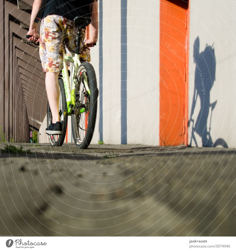 Cyclists with shadow play Cycling tour Legs Wall (building) Colonnades Ground Mountain bike Shorts Sneakers Driving Long Many Emotions Experience Mobility