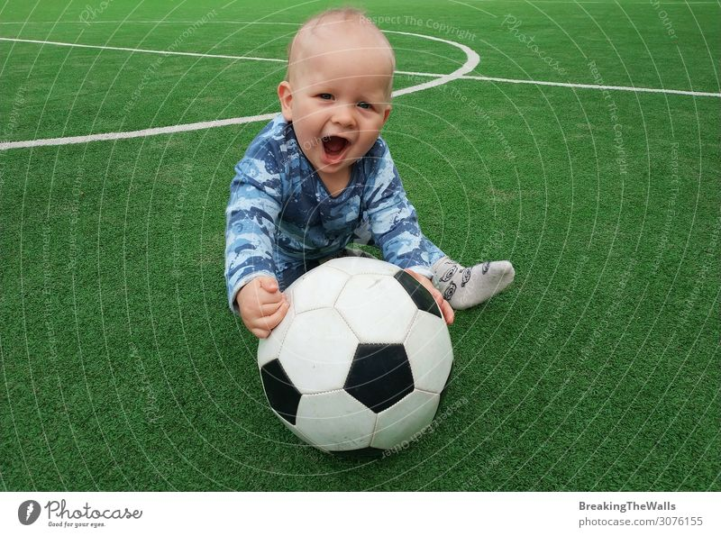 Little boy sitting on green grass of playing field with soccer football ball and looking at camera Lifestyle Leisure and hobbies Sports Soccer Foot ball Ball