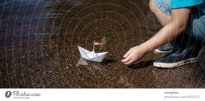 Small boy puts small paper ship in water Joy Happy Healthy Alternative medicine Relaxation Calm Swimming & Bathing Playing Handicraft Model-making