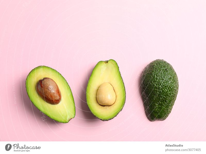 Rip cut avocados with space for text on color background, top view half close exotic slice plant vegetarian backdrop composition ripe summer fruit shape white