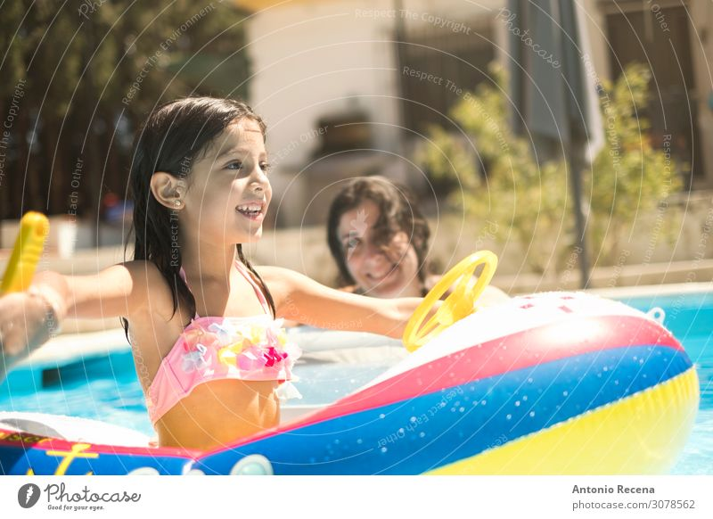 six-year-old girl plays with boat-shaped Lifestyle Joy Swimming pool Playing Summer Child Mother Adults Watercraft Bikini Wet Safety (feeling of) Inflatable