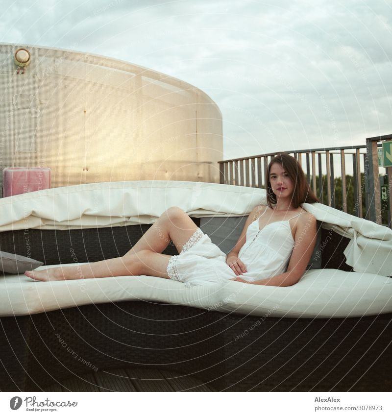 Portrait of a young woman on a sofa of a roof terrace Style Beautiful Wellness Harmonious Sofa Roof Roof terrace Young woman Youth (Young adults) Legs Barefoot