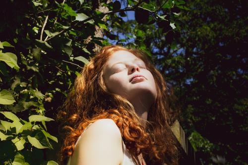 redheaded woman enjoys the sun Tree leaves Contrast Linda Nature Summer daylight To enjoy Green Young woman Red-haired Adults Human being 1 Day Feminine