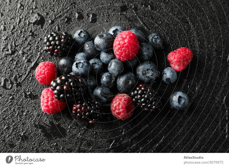 Berries on black cement background with drops,  space for text lay natural dessert bio nature sweet pie summer delicious macro dietary ripe fruits organic raw