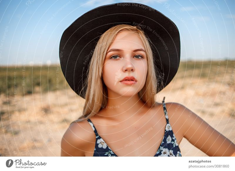 a close-up portrait of a blue-eyed blonde girl in a black hat Black Blonde Blue calm Close-up Dress during Expressive eyes Face Woman Floral glamour Gorgeous