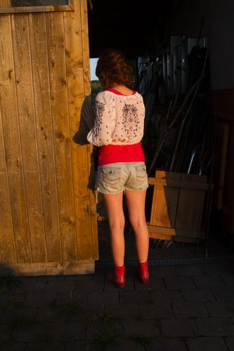 Young woman looks into a dark stable. Human being Feminine girl Youth (Young adults) Infancy House (Residential Structure) hut built door Looking Stand Dream