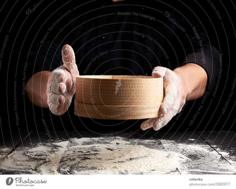 man sifts white wheat flour through a wooden sieve Dough Baked goods Bread Nutrition Table Kitchen Human being Man Adults Hand Sieve Wood Movement Make Fresh