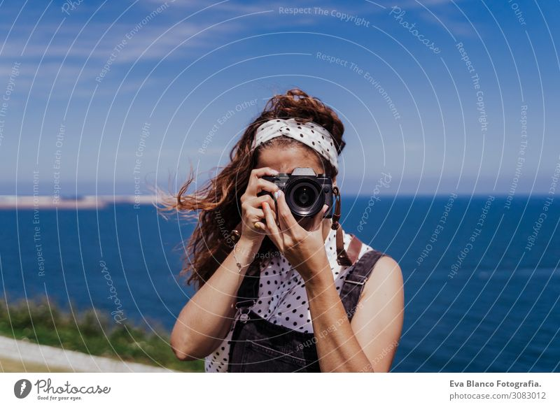 young caucasian tourist woman outdoors taking pictures with a reflex camera on a windy and sunny day. Lifestyle, travel and summertime Caucasian European Spring