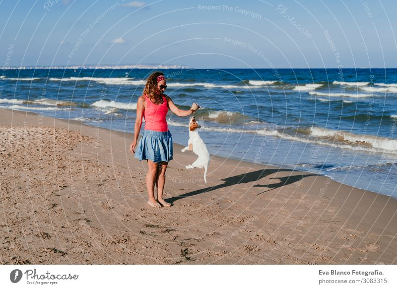 young woman and her cute small jack russell terrier playing at the beach with a tennis ball. Summer and holidays concept Youth (Young adults) Relaxation Blue