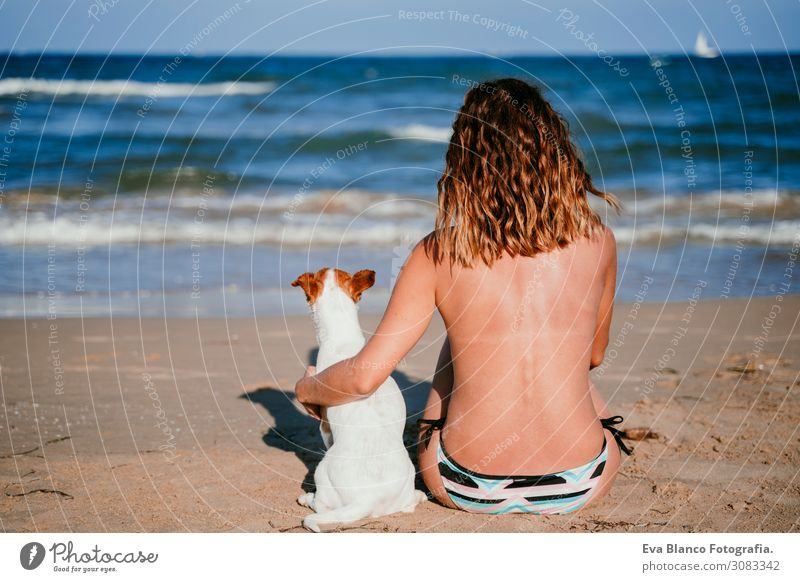 young woman and her cute small jack russell terrier sitting at the beach enjoying and relaxing. Summer and holidays concept Youth (Young adults) Relaxation Blue