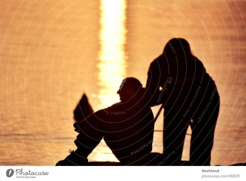 Shoelaces in the evening Sunset Photographer Dusk Man Woman Back-light Water Couple Sit