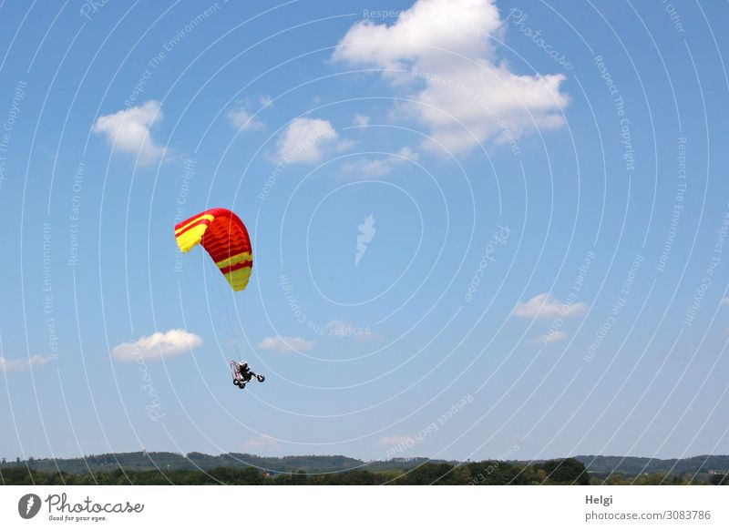 Toy paraglider with hanging vehicle and figure flying in front of a blue sky with clouds Leisure and hobbies Environment Nature Sky Clouds Summer