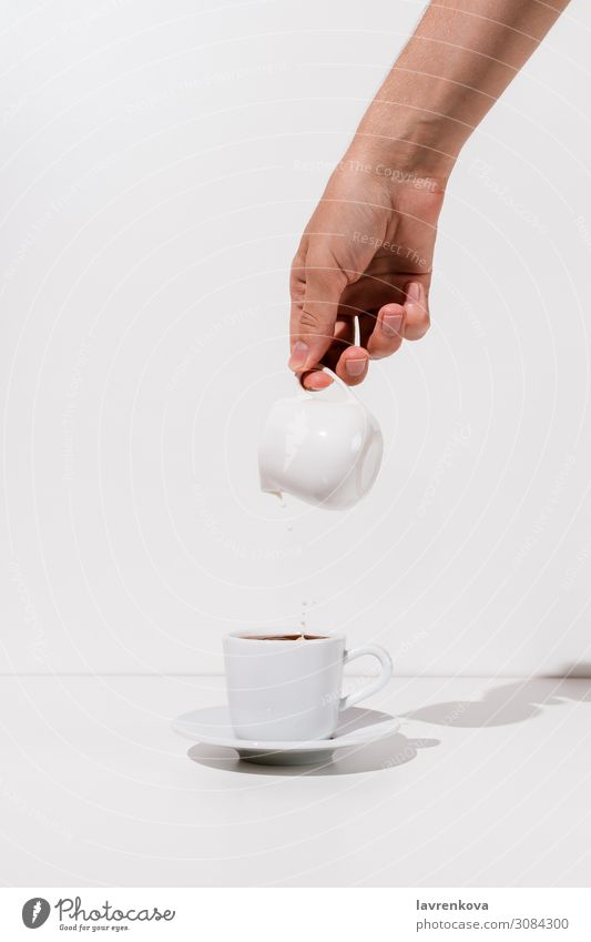 Woman's hand pouring almond milk into cup of coffee Beverage Breakfast Caffeine ceramic creamer Cup Fresh Hand Hot Milk Morning Mug Saucer Tea White
