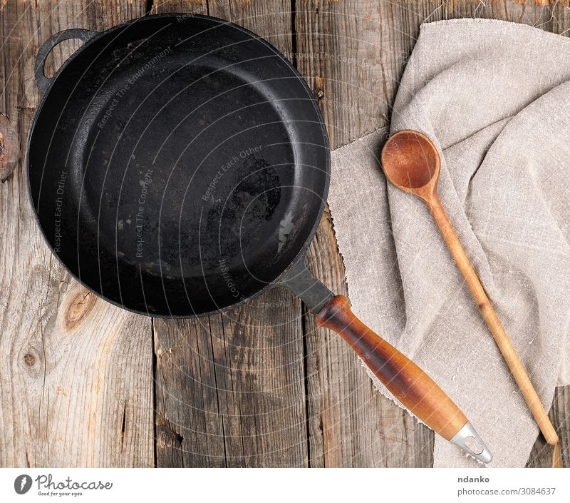 empty black round frying pan with handle and spoon Pan Spoon Table Kitchen Tool Wood Metal Old Above Clean Brown Gray Black background board Cast cooking