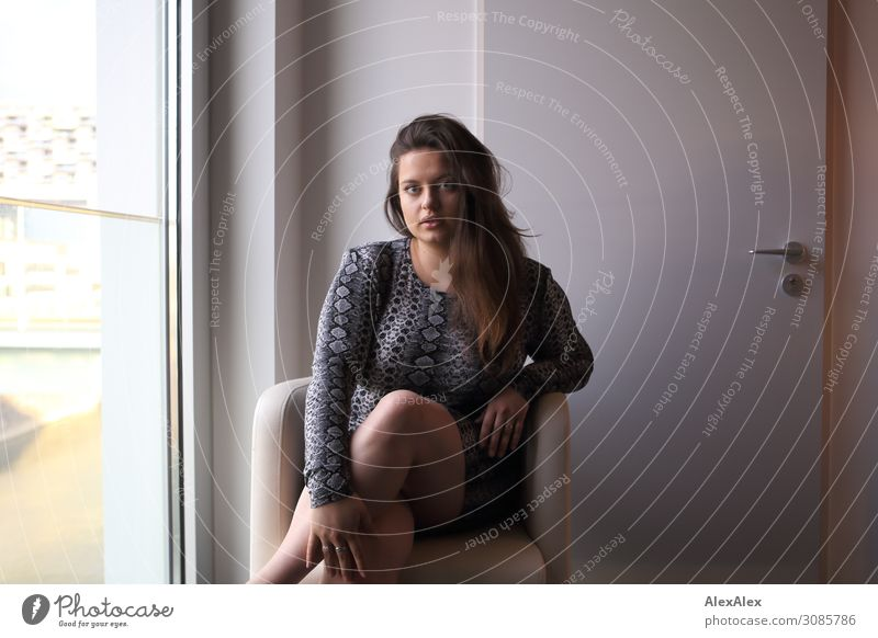 Portrait of a young woman in an armchair Lifestyle Elegant Style Beautiful Armchair Room Hotel room Young woman Youth (Young adults) 18 - 30 years Adults Window