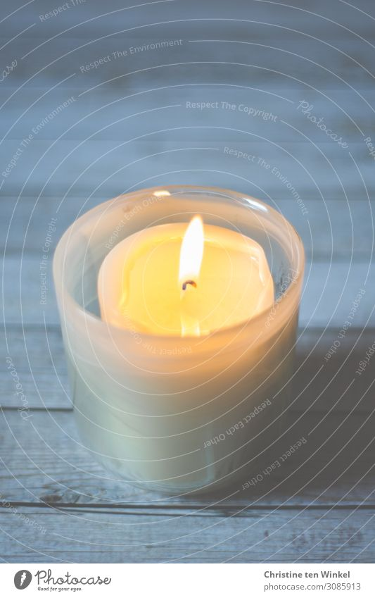 Burning candle in a candle glass on a light wooden background. Weak depth of field shoulder stand Glass Illuminate Simple Bright Warmth Blue Yellow White