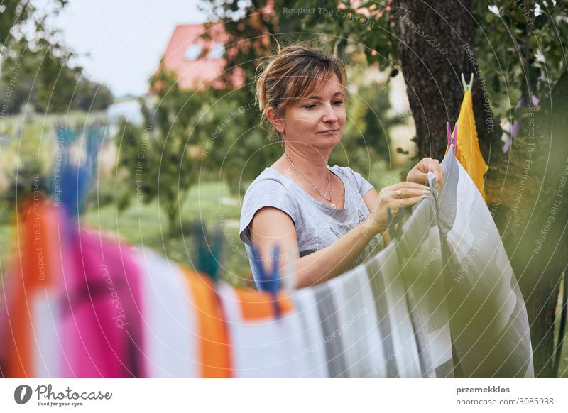 Woman hanging laundered bed linen on clothesline Summer Garden Work and employment Adults 1 Human being 45 - 60 years Clothing Hang Stand Authentic Fresh Wet