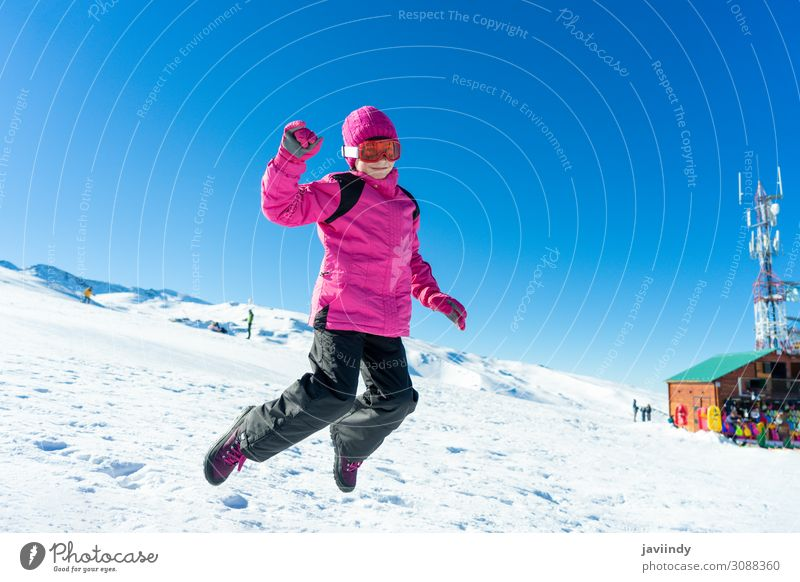 Little girl jumping on the snow at Sierra Nevada ski resort. Joy Happy Relaxation Leisure and hobbies Playing Vacation & Travel Winter Snow Mountain Sports