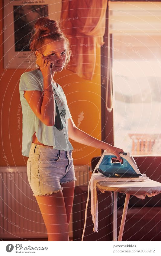 Young woman is ironing her clothes and talking on a smartphone Lifestyle Joy Happy Beautiful House (Residential Structure) To talk Telephone PDA Technology