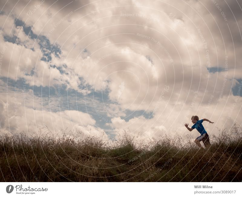 Boy Running Across the Top of a Hill Child Sky Youth (Young adults) Young man Clouds Grass Boy (child) Copy Space Field Youth culture Running sports