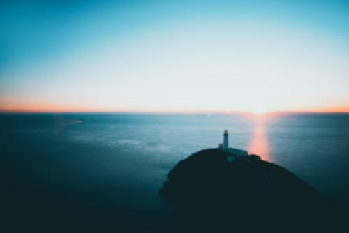 dreamy - a lighthouse and the setting sun on the horizon Lighthouse Deep depth of field Blur blurred blurred background hazy Dream Horizon Ocean ocean vacation