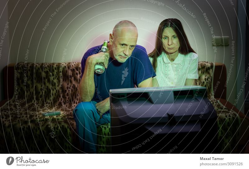 Middle-aged man and woman, watch television, looking sad Drinking Alcoholic drinks Beer Lifestyle Face Relaxation Leisure and hobbies Sofa Entertainment